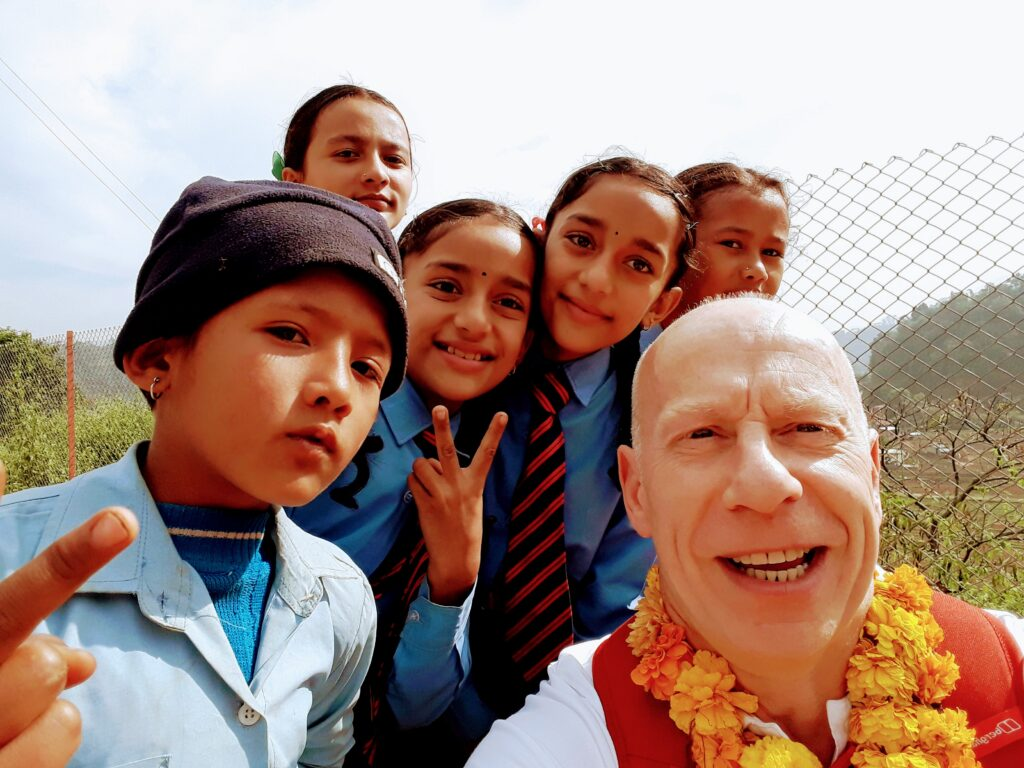 Our Rotarian Derrick R. with some school children during Nepal visit
